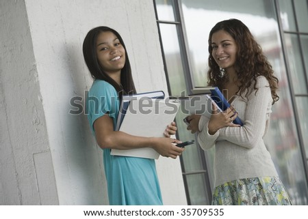 Portrait of two teenage girls holding books and smiling in a school - stock photo