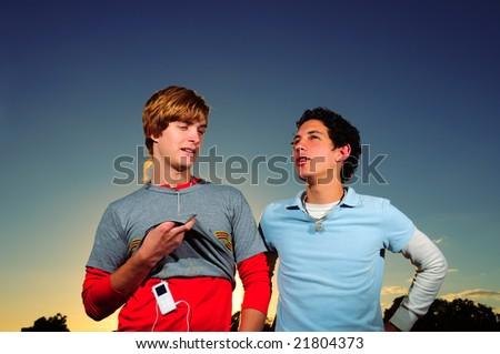 Portrait of two trendy teenager friends talking - stock photo