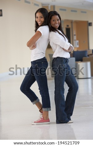 Portrait of two university students back to back in a college hallway - stock photo