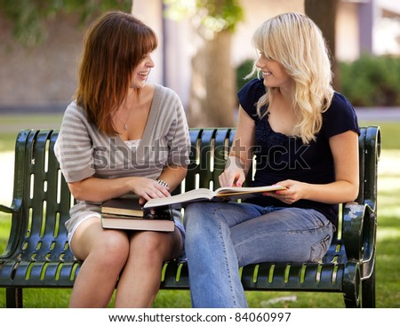 Portrait of two university students studying outdoors on a park bench - stock photo