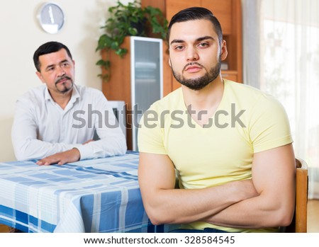 Portrait of two upset despair male adults arguing about something in living room - stock photo