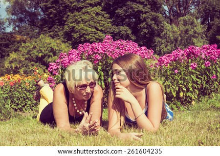 Portrait of two women in the summer outdoors. Mother and daughter talking in the park. Photo toned. - stock photo