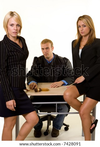 Portrait of two women lawyers sitting in front of a male judge looking forward