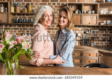 Portrait of two women, senior and young hugging in kitchen