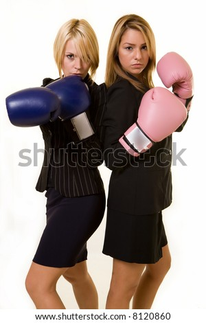 Portrait of two women wearing business attire and each wearing a pair of boxing gloves