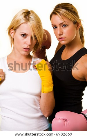 Portrait of two women wearing shorts and tank top one wearing pink boxing gloves and one wearing yellow hand wraps - stock photo