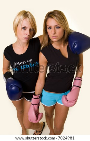 Portrait of two women wearing shorts and tshirts one wearing pink boxing gloves and one wearing blue