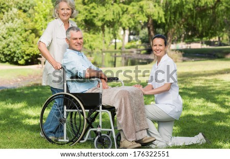Portrait of two women with a mature man sitting in wheel chair at the park - stock photo