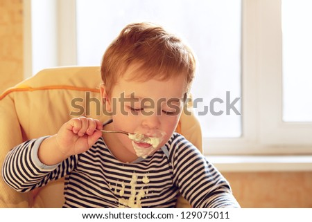 Portrait of two year old boy eating porridge in the morning. - stock photo
