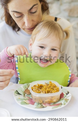 portrait of two years age blonde baby with green bib eating rice paella from tupperware sitting on legs of mother woman in white table - stock photo