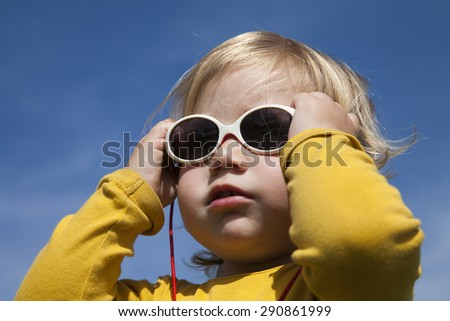 portrait of two years aged blonde happy baby yellow shirt with white kid sunglasses and blue sky background - stock photo