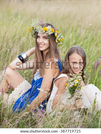 Portrait of two young beautiful cute romantic happy girl wearing a wreath of wild flowers in summer day, outdoors. Friends Giving One Another Hug. Series of photos - stock photo