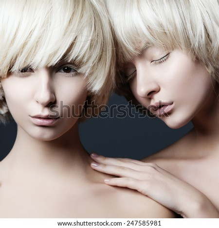 Portrait of two young beautiful girls twins in the studio, closeup - stock photo