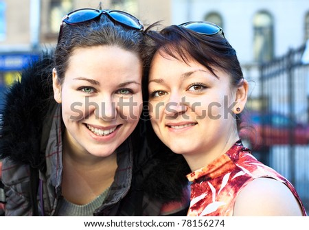Portrait of two young beautiful women a girlfriend. Standing together. Looking at camera and smiling - stock photo