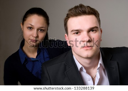 Portrait of two young business partners on a gray background - stock photo