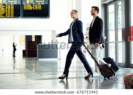Portrait of two young business partners walking and talking through the airport hall.