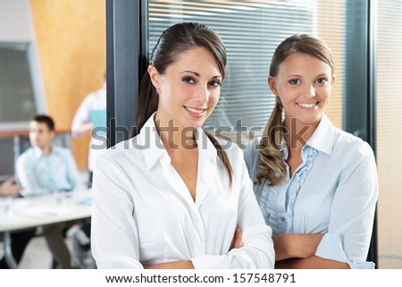 Portrait of two young business woman standing while his team talks in the background  - stock photo