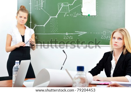 Portrait of two young business women at their office working near desk using papers laptop board microphone water and other tools