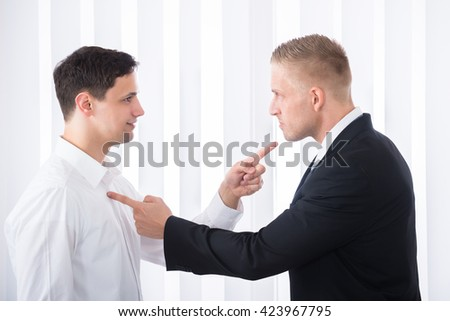 Portrait Of Two Young Businessmen Pointing Finger At Each Other