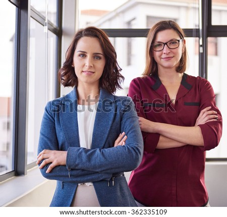 Portrait of two young businesswomen colleagues in an office next to large windows standing confidently with their arms crossed and looking at the camera with expressions of positivity - stock photo
