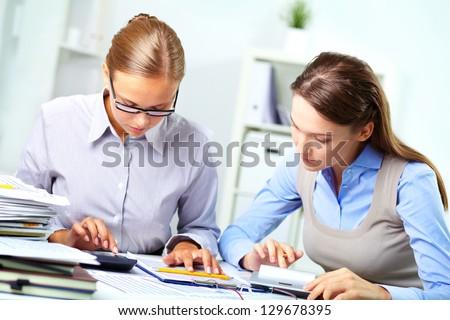 Portrait of two young businesswomen working with calculators in office - stock photo