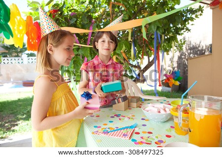 Portrait of two young children girls friends together at a birthday party table with sweets and juice in a decorated home garden, smiling outdoors holding gifts. Summer holiday celebration lifestyle. - stock photo