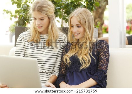 Portrait of two young fashion blogger working online, sitting at cafe. City life.  - stock photo