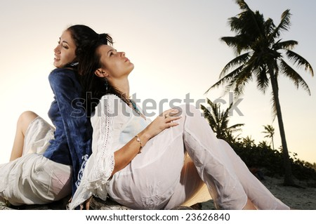 Portrait of two young female friends relaxing on the beach at sunset - stock photo