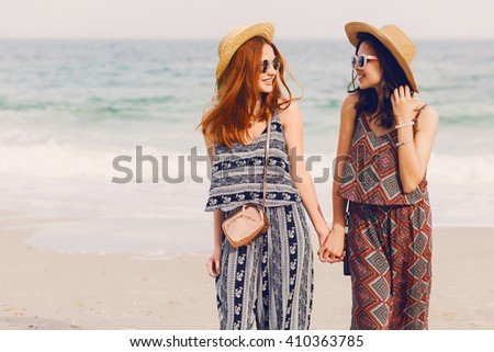 Portrait of  two young female friends walking on the sea shore looking at camera laughing, talking. Sisters  strolling along a beach. Stylish summer beachwear, straw hat , sunny colors.  - stock photo