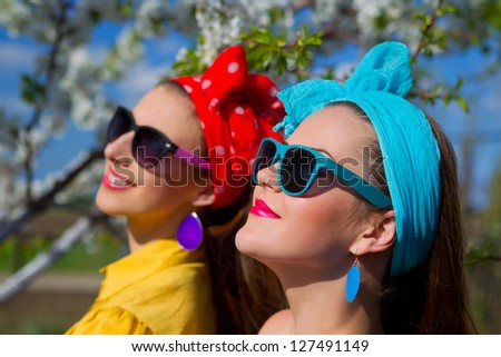 Portrait of two young female on garden - stock photo