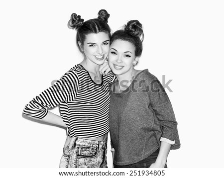 Portrait of two young girl standing together and smiling. Top knot hairdo. White background, not isolated. Inside - stock photo