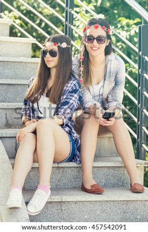 Portrait of two young girlfriends on summer vacation taking photos with smart phone and vintage camera.They are sitting on the outdoors stairs and smiling to camera. Girls are wearing matching outfits