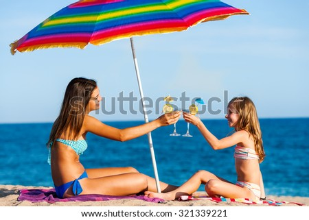 Portrait of two young girls on summer holiday. Young women sitting under colorful umbrella on beach drinking fruit cocktails. - stock photo