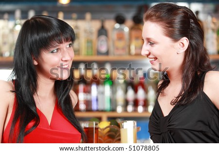 Portrait of two young girls sitting in a bar - stock photo