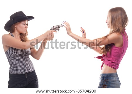 Portrait of two young girls with a gun shooting studio - stock photo