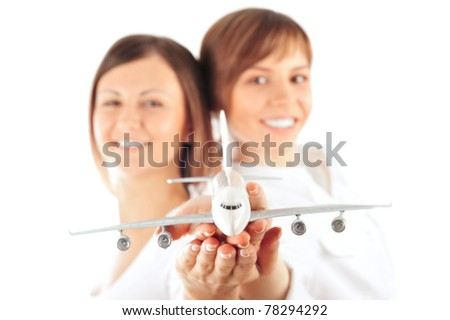 Portrait of two young happy women stewardess holding jet aircraft in her arms on foreground. Advertisement banner for transport companies