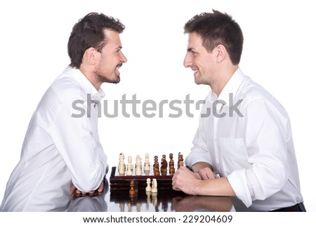 Portrait of two young men are playing chess on the white background and are looking at each other. - stock photo