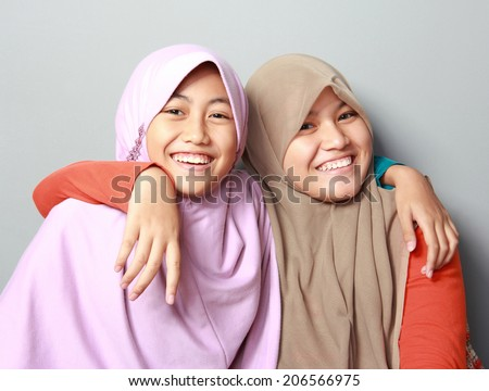 portrait of two young muslim girl best friend having smiling together on grey background