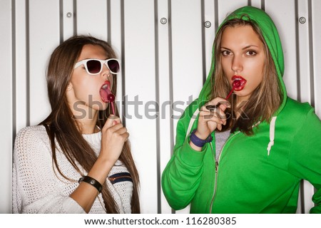 Portrait of two young naughty girls sucking lollipops, outdoors - stock photo