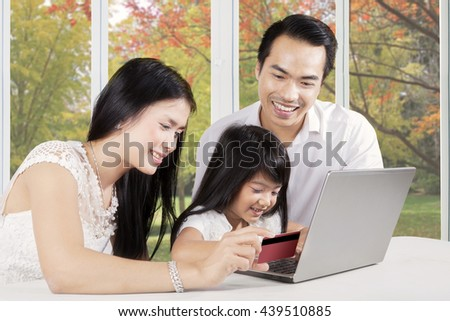 Portrait of two young parents and their daughter using credit card and laptop computer for shopping online at home - stock photo