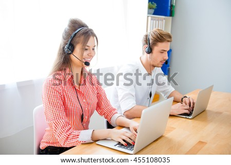Portrait of two young people in headphones working with laptops
