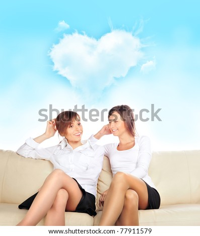 Portrait of two young pretty girls sitting relaxed on sofa discussing their relations with boys - stock photo
