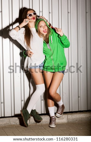 Portrait of two young sensual girls sucking lollipops, outdoors - stock photo