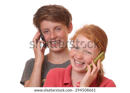 Portrait of two young teenagers talking with cell phones - stock photo