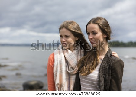 Portrait of two young women, friends at the coast. Caucasian lifestyle concept.