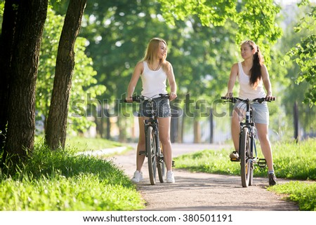 Portrait of two young women girlfriends wearing jeans shorts sitting on bikes on sidewalk in park on sunny summer day, talking, having fun together - stock photo