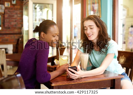 Portrait of two young women sitting at cafe with mobile phone