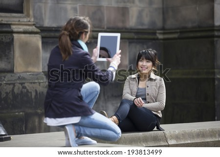 Portrait of two young women taking pictures of themselves through Tablet. Caucasian and Chinese friends taking photo with Tablet. - stock photo