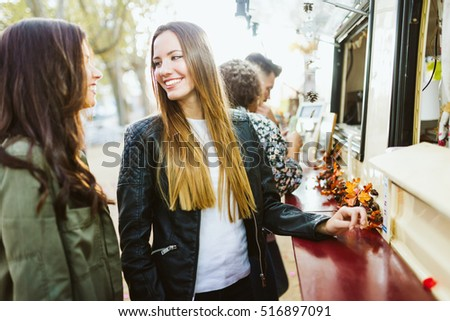 Portrait of two young women visiting eat market in the street.