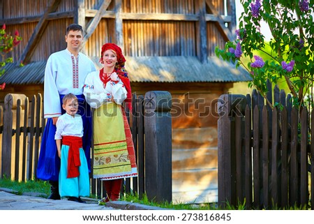 portrait of ukrainian family dressed in traditional costumes near the house - stock photo